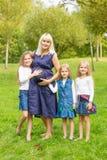 有她的三个女儿的年轻人怀孕的母亲在公园 免版税库存图片