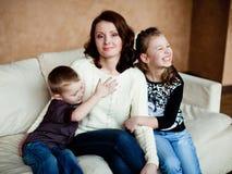 有她的两个孩子的妈妈坐长沙发 免版税库存照片