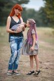 有她的两个孩子的愉快的母亲步行的在公园 库存图片