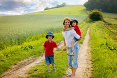 有她的两个孩子的年轻母亲春天开花的领域的  免版税库存图片