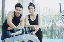 有她的个人健身教练员的妇女在健身房 库存图片