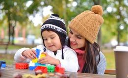 有她的使用与五颜六色的塑料块的孩子的少妇 免版税库存照片