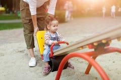 有她的使用在孩子的五颜六色的操场的女婴的愉快的年轻母亲 有小孩的妈妈获得乐趣在夏天公园 免版税库存图片