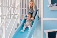 有她的使用在孩子的五颜六色的操场的男婴的愉快的年轻母亲 库存图片