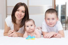 有她的使用在床上的两个儿子的年轻妈妈 免版税库存图片