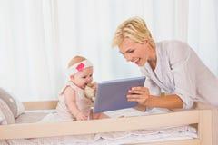 有她的使用数字式片剂的女婴的愉快的母亲 免版税库存照片