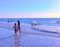 有她的儿子的妇女,走和享受在克利尔沃特海滩的日落 免版税图库摄影