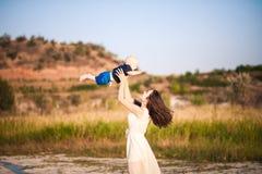 有她的儿子的年轻母亲在日落背景的海滩的 库存图片