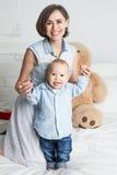 有她的儿子的愉快的母亲在床上 图库摄影