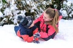 有她的儿子的愉快的母亲在雪的胳膊容忍的 免版税库存照片