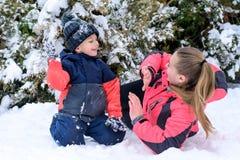 有她的儿子的愉快的母亲在雪的胳膊容忍的 免版税图库摄影