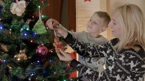 有她的儿子的愉快的白肤金发的母亲在圣诞树下 股票视频