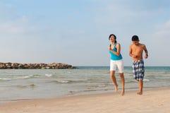 有她的儿子的母亲在海滩跑 库存图片