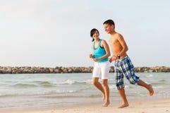 有她的儿子的母亲在海滩跑 免版税库存图片