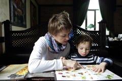 有她的儿子的母亲在餐馆 库存图片