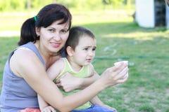 有她的儿子的母亲她的胳膊的 免版税库存图片