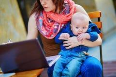 有她的儿子的年轻工作母亲咖啡馆的 库存照片