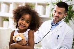 有她的儿科医生的美丽的微笑的美国黑人的女孩 库存图片