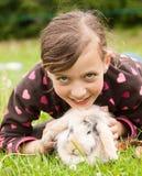有她的兔子宠物的年轻微笑的女孩 免版税库存图片