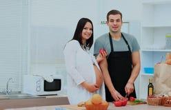 有她的准备食物的丈夫的孕妇 他切开菜,她拿着苹果 库存图片