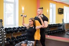 有她的在健身房行使与杠铃的个人健身教练员的妇女力量体操 图库摄影