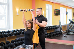 有她的在健身房行使与杠铃的个人健身教练员的妇女力量体操 库存图片