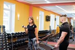 有她的在健身房行使与杠铃的个人健身教练员的妇女力量体操 免版税图库摄影