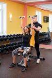 有她的在健身房行使与杠铃的个人健身教练员的妇女力量体操 库存照片