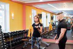 有她的在健身房行使与杠铃的个人健身教练员的妇女力量体操 免版税库存图片