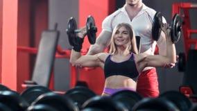 有她的在健身房行使与杠铃的个人教练员的妇女 库存照片