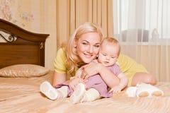 有她的在家使用在床上的小女儿的年轻母亲 免版税库存照片