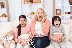 有她的在家吃玉米花和观看电影在长沙发的孙的年轻美丽的祖母 免版税库存照片