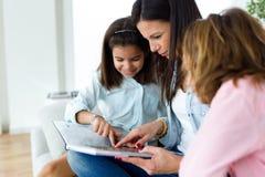 有她的在家读书的女儿的美丽的母亲 免版税库存图片