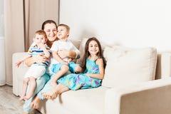有她的坐和摆在为家庭照片的孩子的妈妈 免版税库存照片