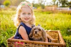 有她的坐在一个柳条筐的狗的愉快的儿童女孩 免版税图库摄影