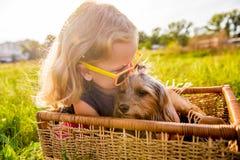 有她的坐在一个柳条筐的狗的愉快的儿童女孩 免版税库存照片