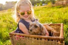 有她的坐在一个柳条筐的狗的愉快的儿童女孩 库存照片