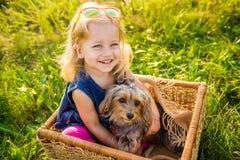 有她的坐在一个柳条筐的狗的愉快的儿童女孩 库存图片
