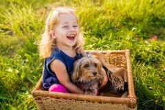 有她的坐在一个柳条筐的狗的愉快的儿童女孩 免版税库存图片
