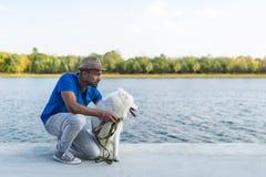 有她的坐由河的狗白色萨莫耶特人的愉快的年轻斯里兰卡的人 库存图片