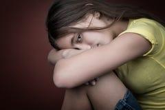 有她的基于她的腿的头的哀伤的女孩 免版税库存图片