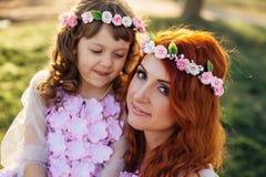 有她的基于自然的女儿的年轻红发母亲在阳光下 免版税库存图片