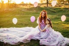 有她的基于自然的女儿的年轻红发母亲在阳光下 免版税库存照片