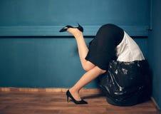 有她的头的妇女在垃圾桶 免版税库存图片