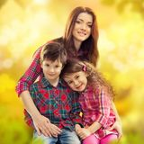 有她的女儿和儿子的愉快的母亲 免版税图库摄影