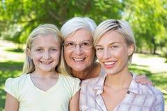 有她的女儿和祖母的愉快的金发碧眼的女人 库存图片