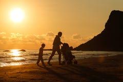 有她的女儿和婴孩的母亲一个沙滩的 库存图片