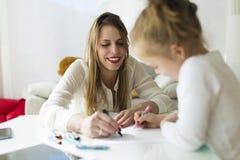有她的女儿图画的美丽的母亲与蜡笔在家 免版税库存照片