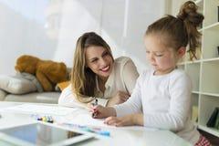 有她的女儿图画的美丽的母亲与蜡笔在家 库存照片