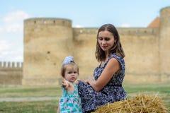 有她的女儿的一个年轻母亲坐秸杆在堡垒附近 库存图片